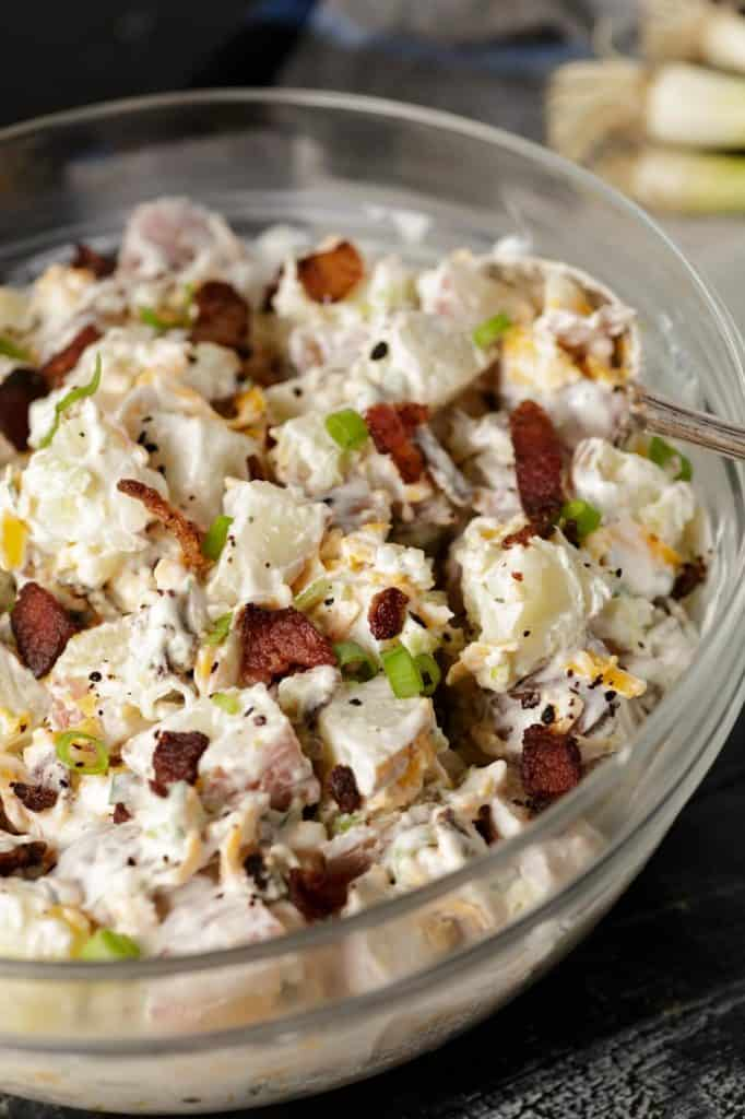 A bowl of potato salad with ranch dressing and bacon on top