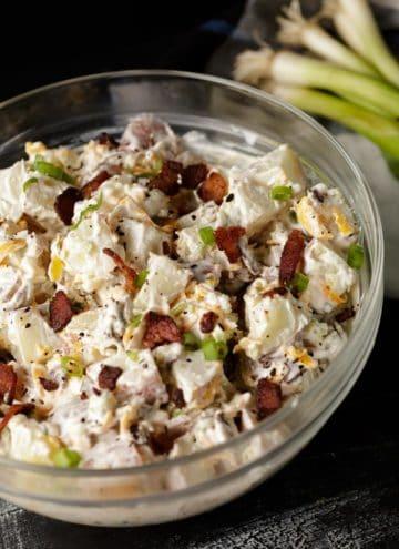 A glass bowl of loaded potato salad