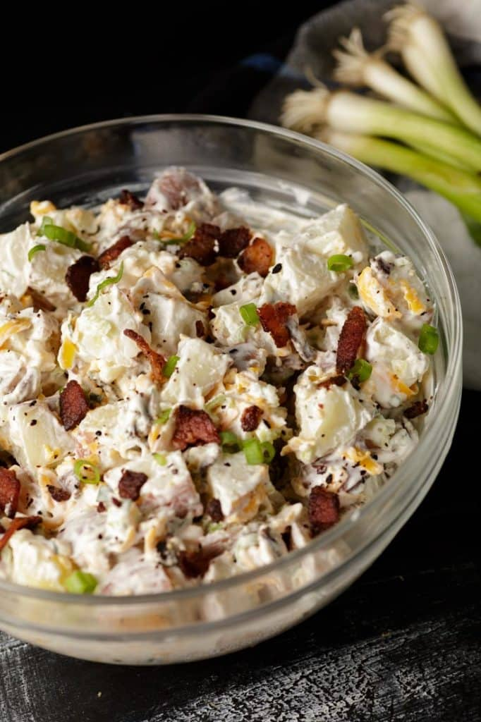 A glass bowl of loaded potato salad