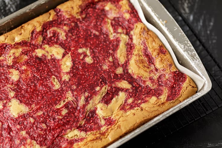 Baked white chocolate raspberry bars in a baking dish