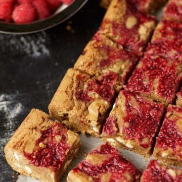 A batch of raspberry blondies on parchment paper
