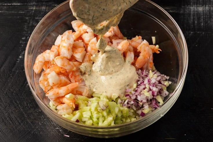 Dressing being poured over shrimp salad