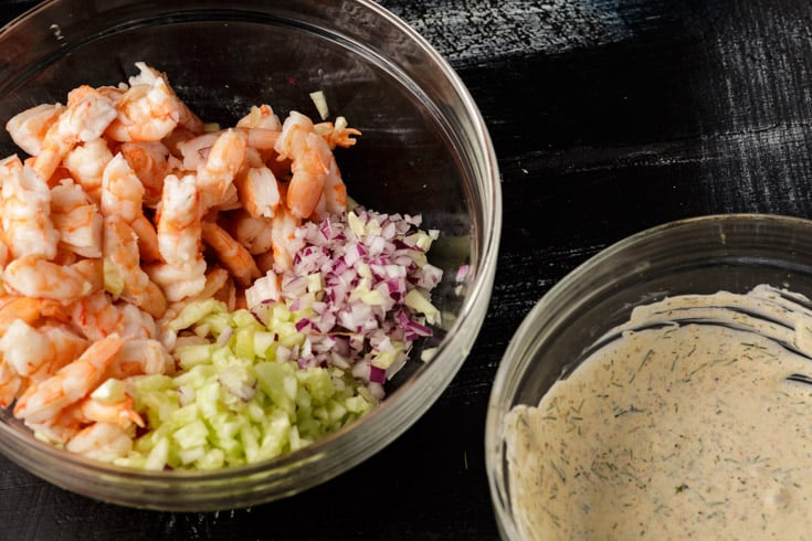 A bowl of shrimp, onion and cucumber next to a bowl of dressing