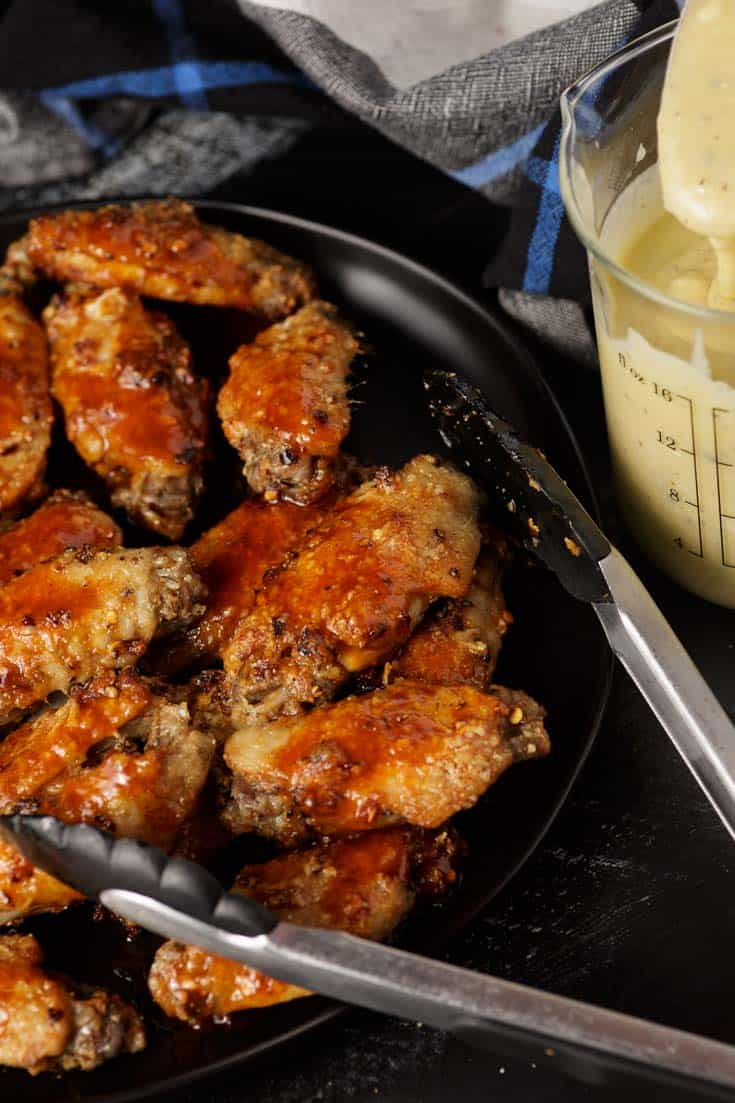 A platter of buffalo wings with dipping sauce on the side