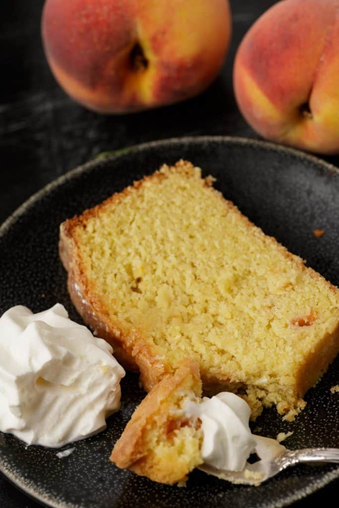 A slice of peach pound cake with whipped cream