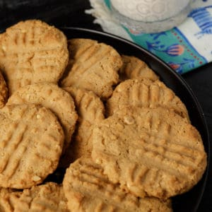A platter of peppery peanut butter cookies with a glass of milk