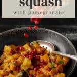 A bowl of butternut squash salad with pomegranate seeds being sprinkled on top