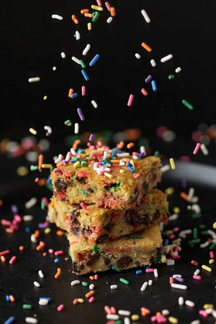 A stack of blondies with sprinkles fall on them
