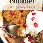 A baking dish of apple cobbler with whipped cream and pomegranates