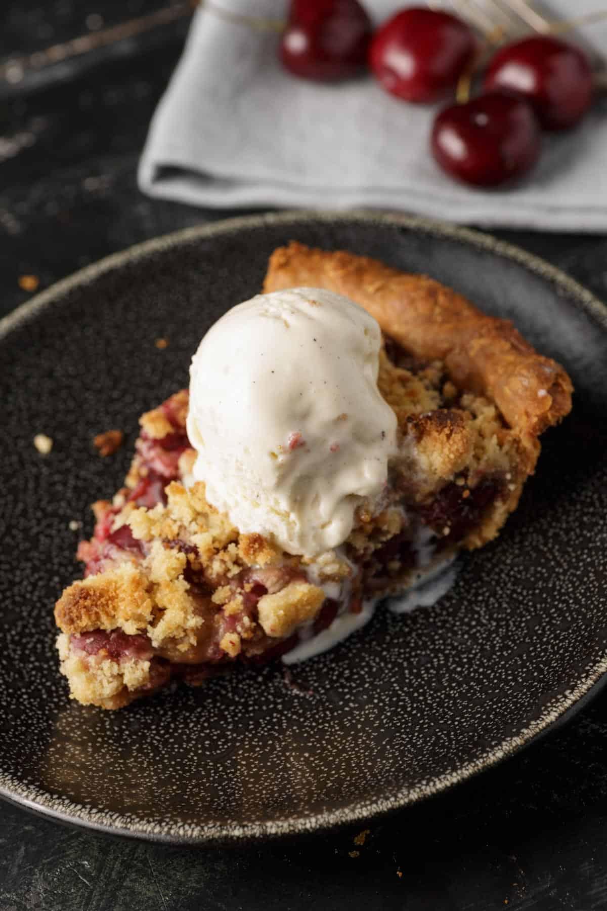 A slice of cherry pie covered in ice cream