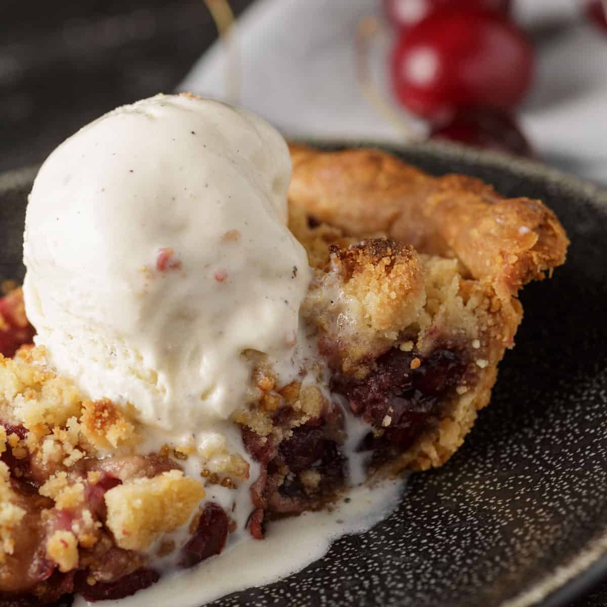 A slice of cherry streusel pie with vanilla ice cream