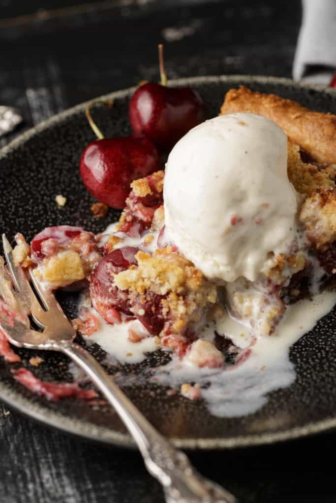 A dish of cherry pie with ice cream melting on the top