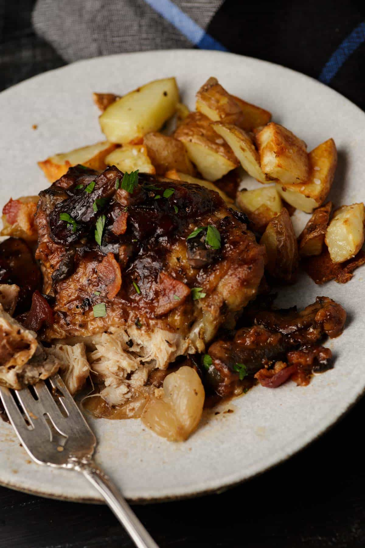 A fork full of coq au vin with roasted potatoes