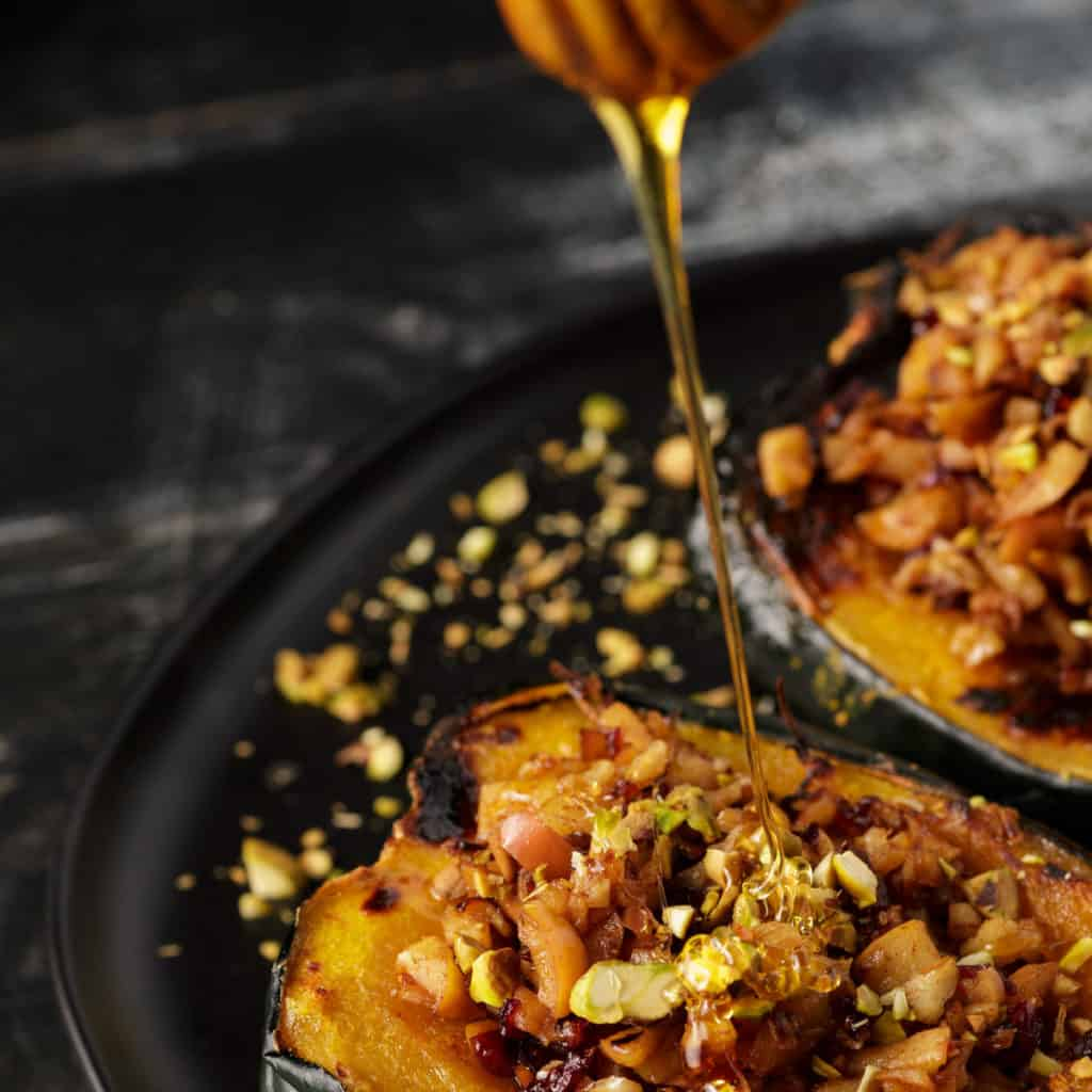 Honey being drizzled over stuffed acorn squash