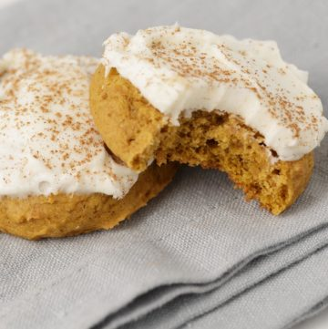 Two soft pumpkin cookies with cream cheese frosting.