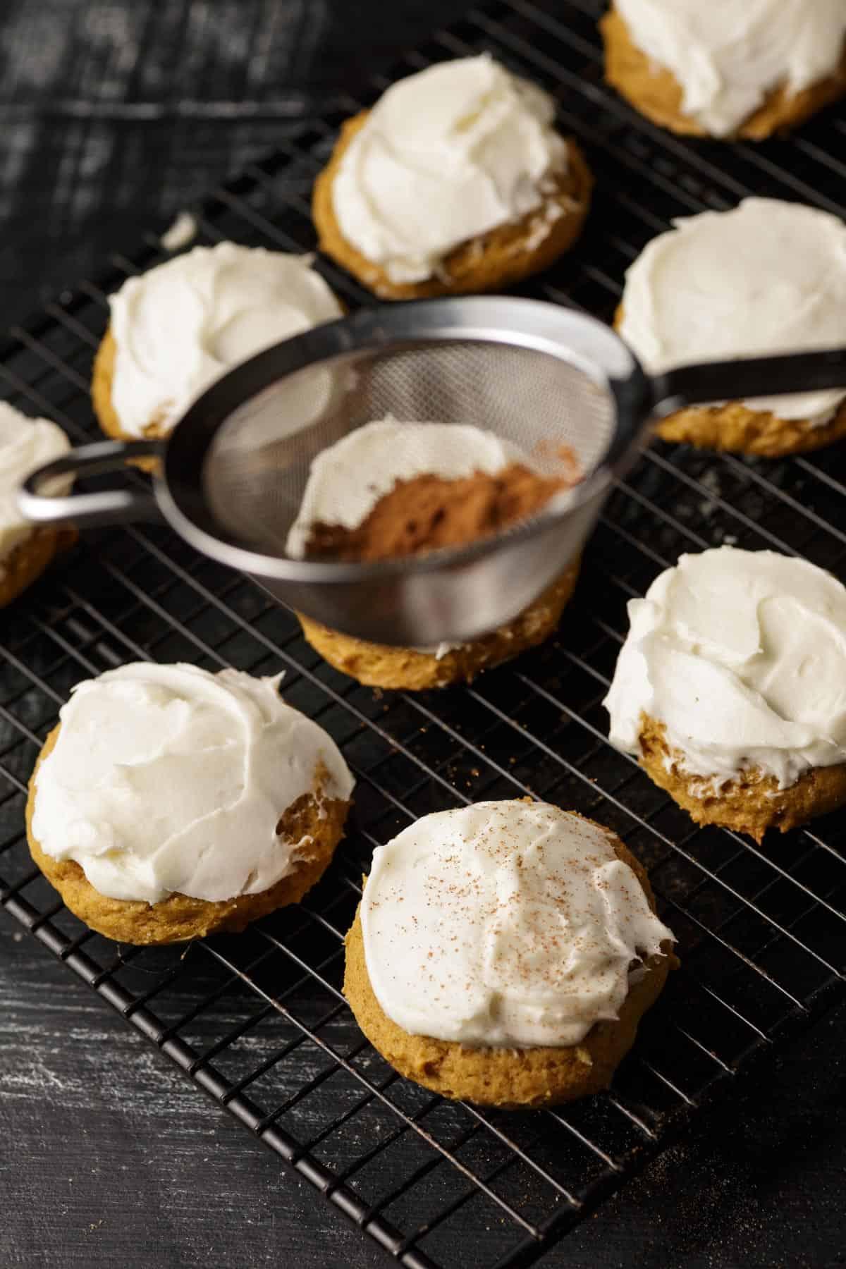 Pumpkin spice being sprinkled on cookies