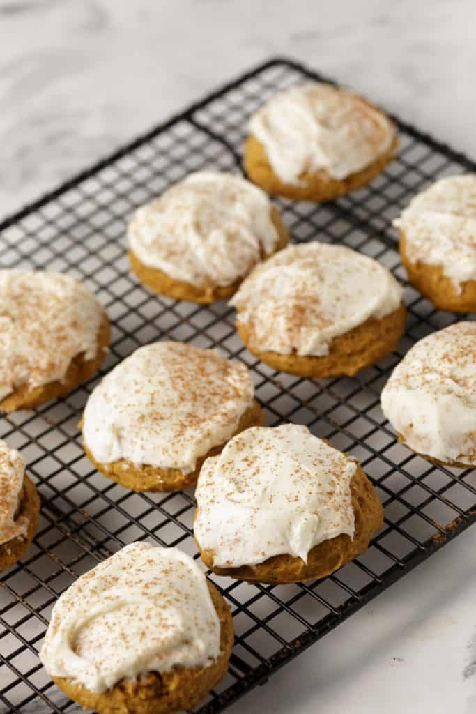 Iced pumpkin cookies on a cooking rack