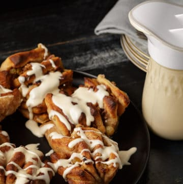 A plate of apple cinnamon rolls with a pitcher of caramel frosting