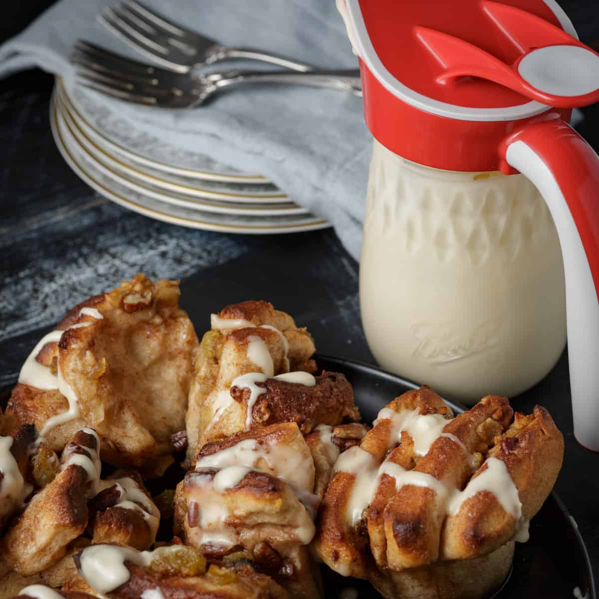 A platter of apple cinnamon rolls with a pitcher of frosting
