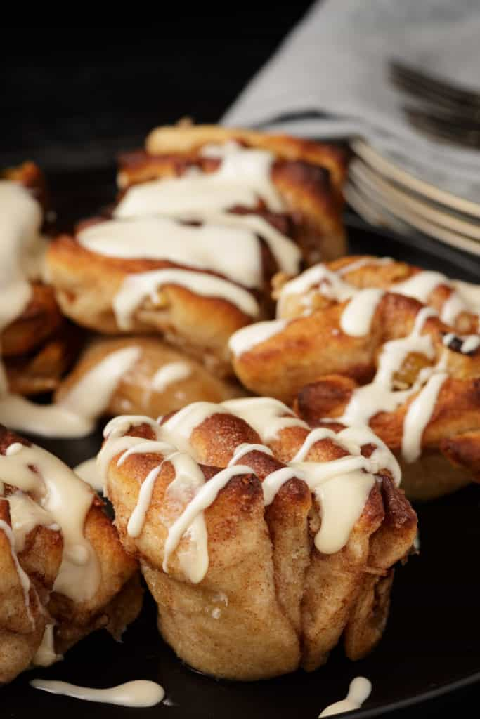 Frosted apple cinnamon rolls on a platter