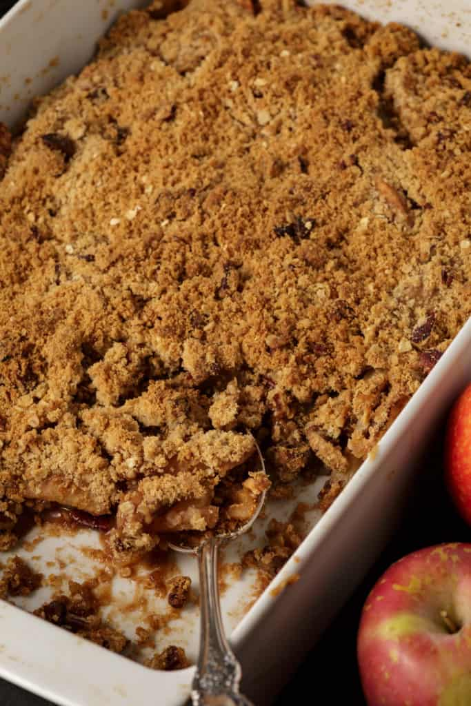 A baking dish of apple crisp with a spoon full removed