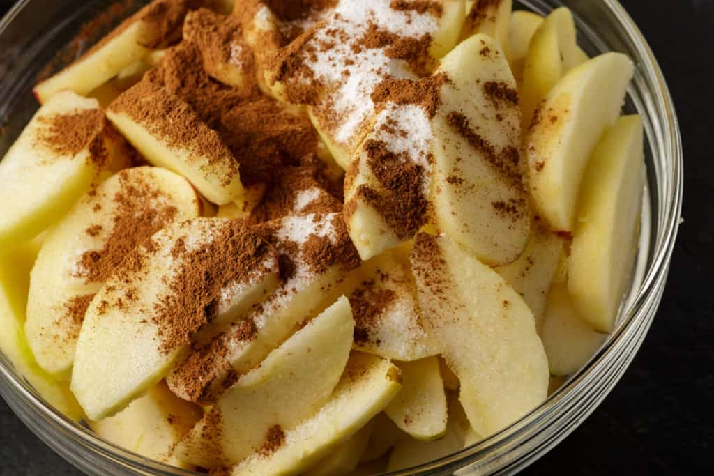 A bowl of sliced apples with cinnamon and sugar