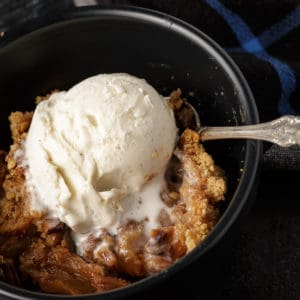 A bowl of apple crisp with a scoop of ice cream