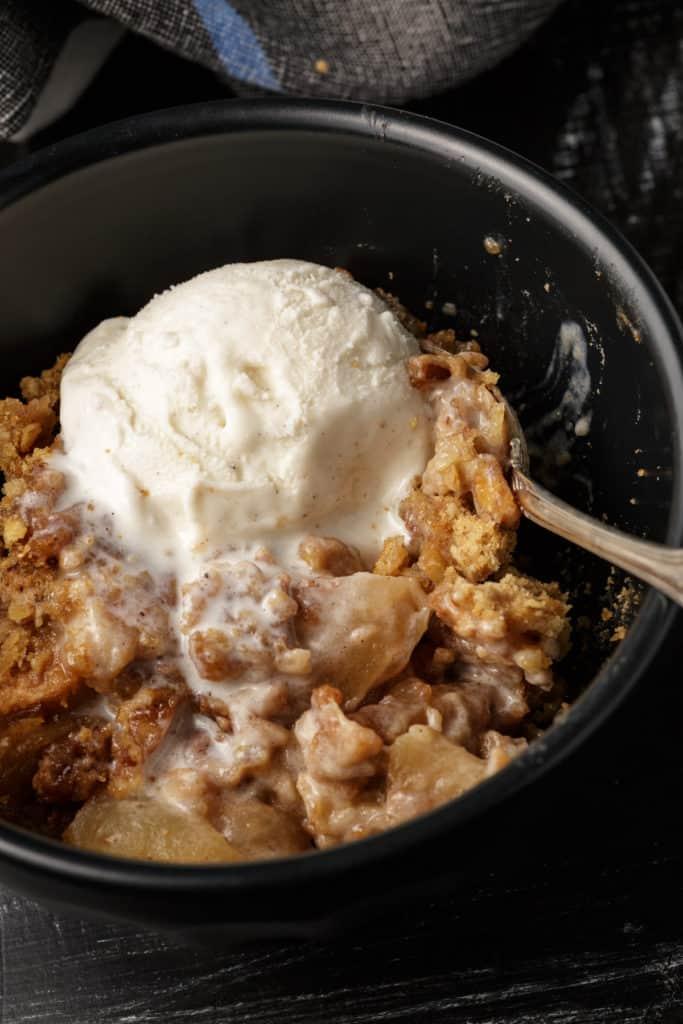A spoon full of apple crisp with ice cream