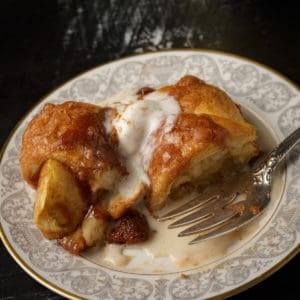 A plate of apple dumplings with melted ice cream