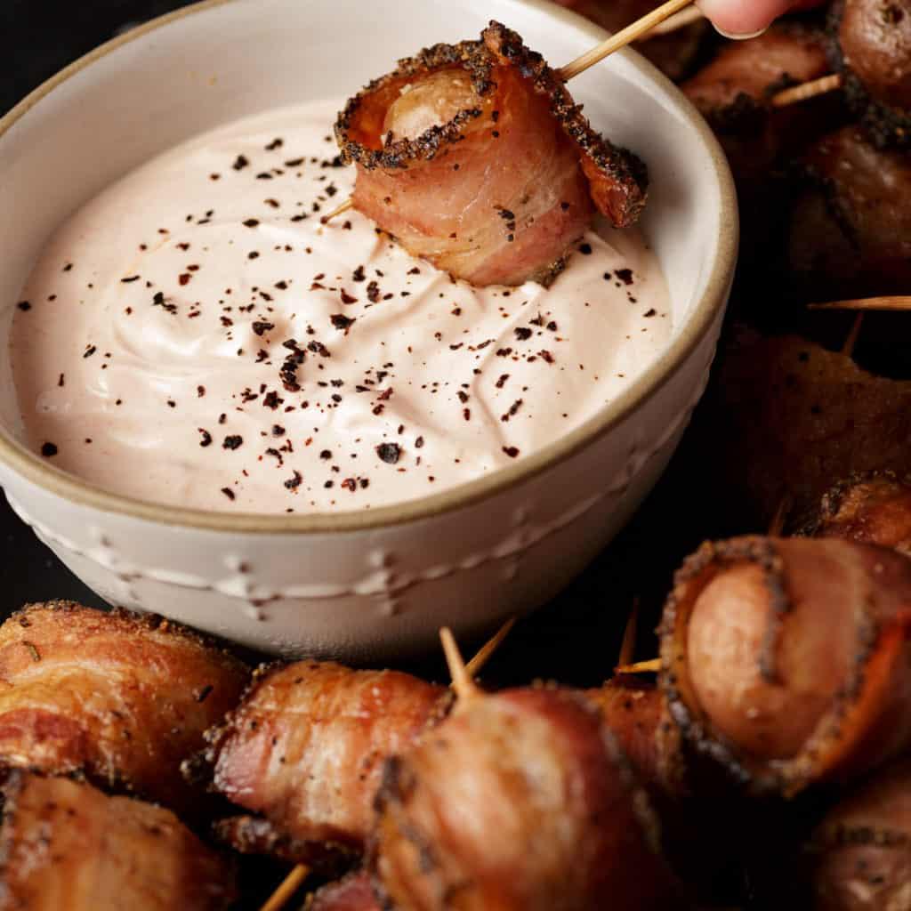 A bowl of dip with bacon wrapped potato bites around it