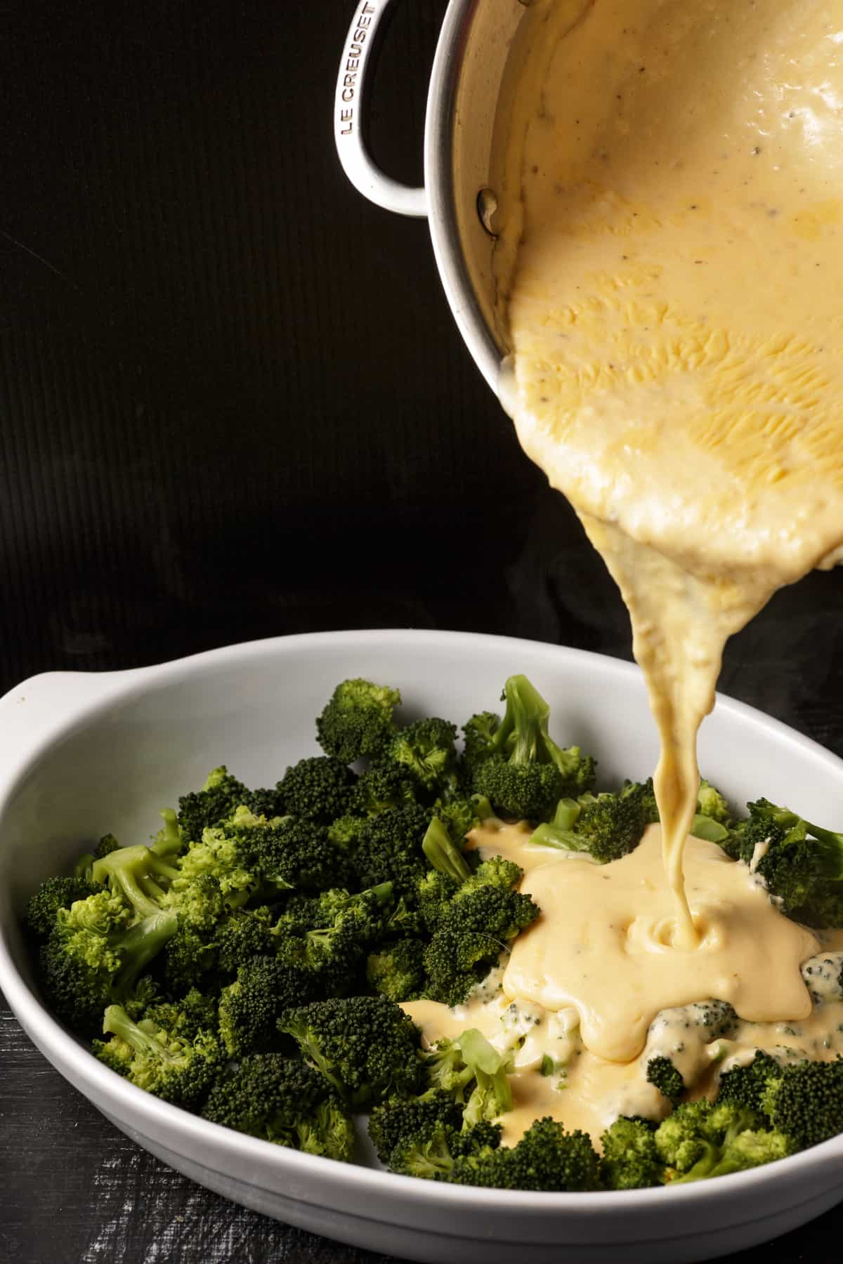 Cheese sauce being poured over broccoli