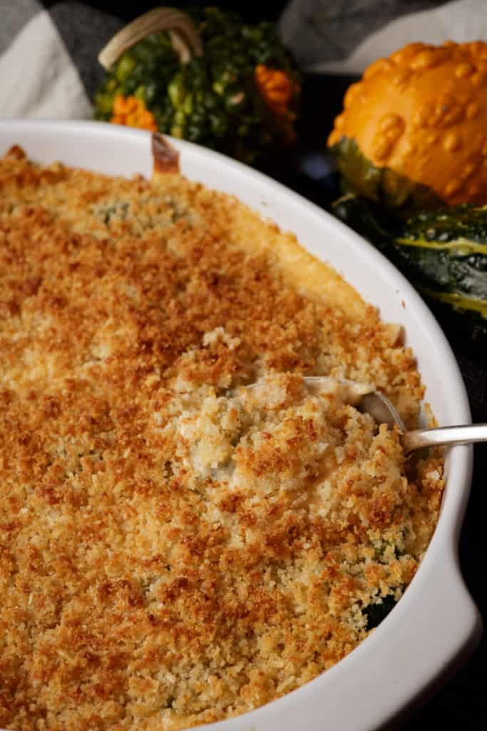 A serving spoon in a dish of baked broccoli casserole