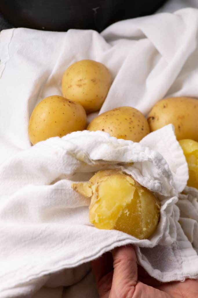 Rubbing the skin off potatoes