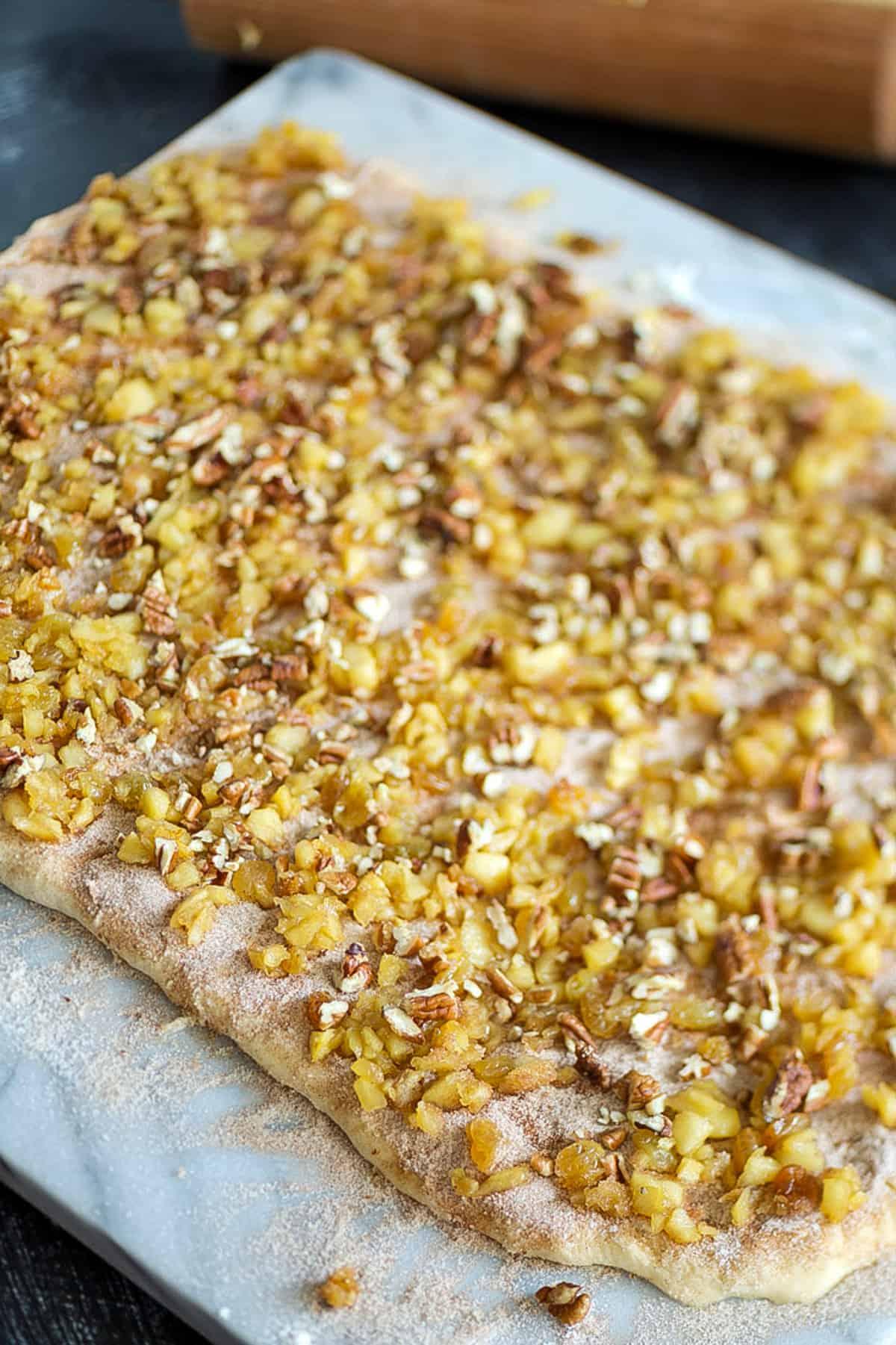 apples and raisins on cinnamon roll dough