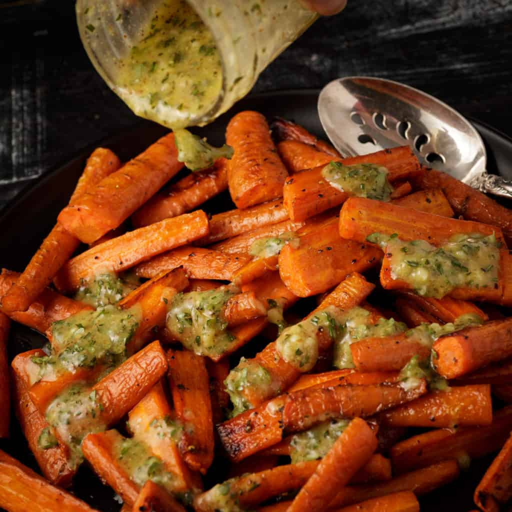 Dressing being poured over roasted carrots
