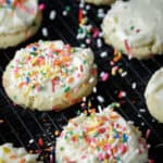 Frosted sprinkle cookies with sprinkles being added