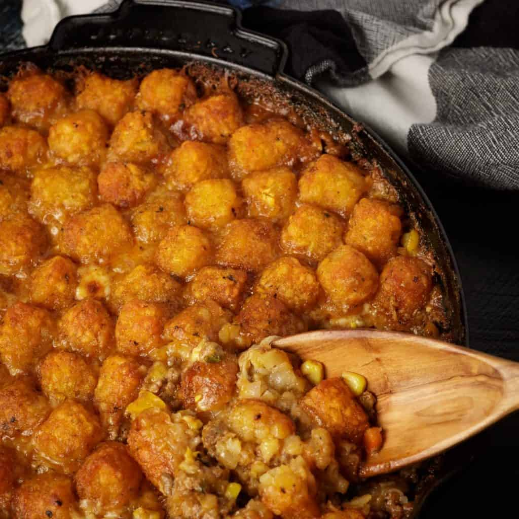 A wooden spoon scooping out tater tot casserrole
