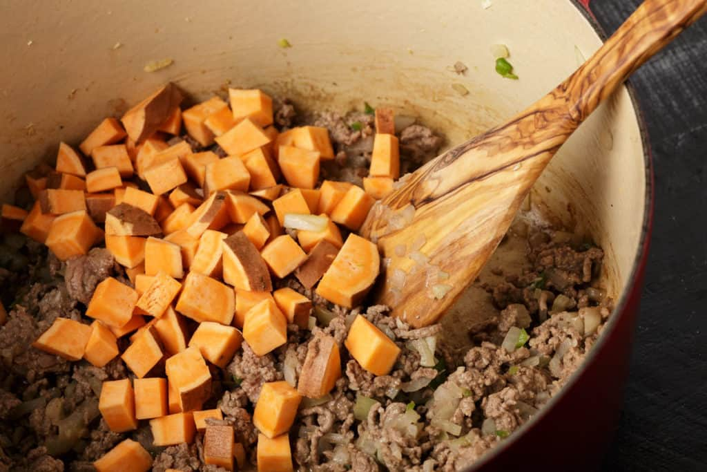 A dutch oven with browned beef and sweet potatoes