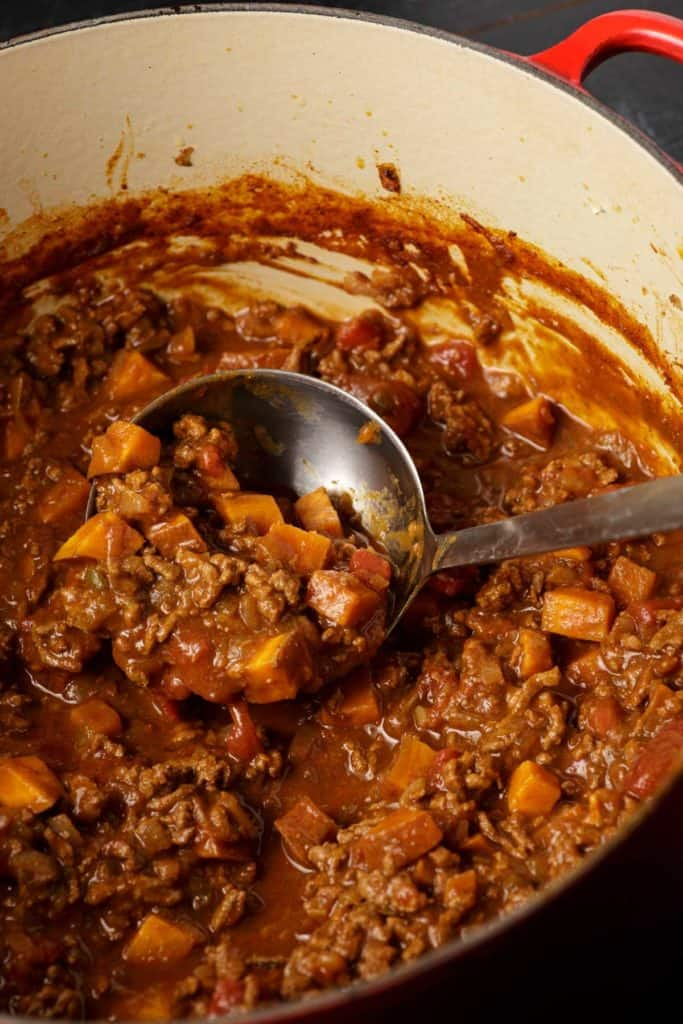 A dutch oven with a ladle full of chili