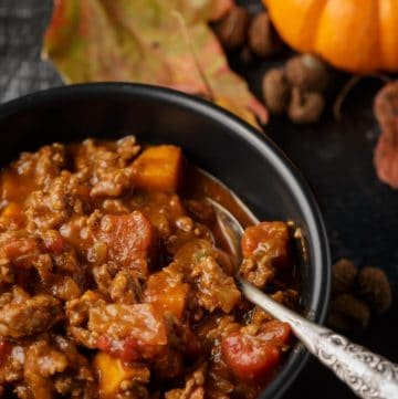 A bowl of chili with sweet potatoes with a spoon