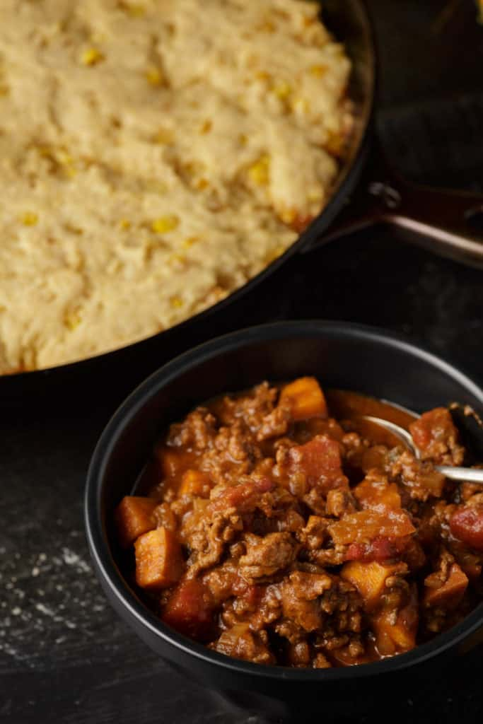 A bowl of sweet potato chili with a pan of cornbread