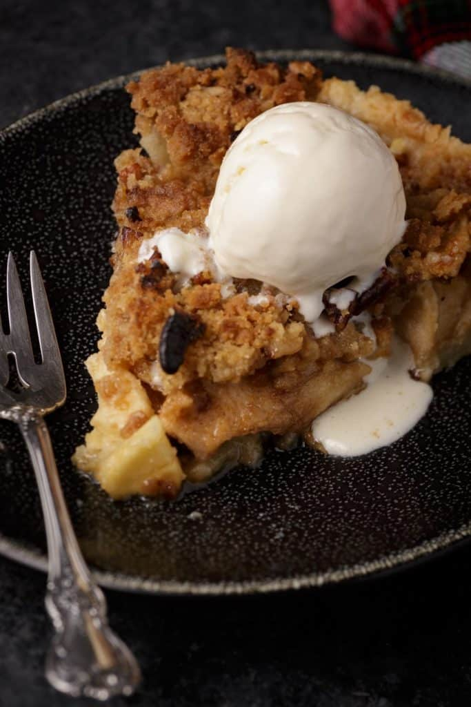A slice of baked apple pie with ice cream