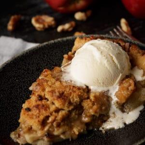 A slice of homemade apple pie with vanilla ice cream