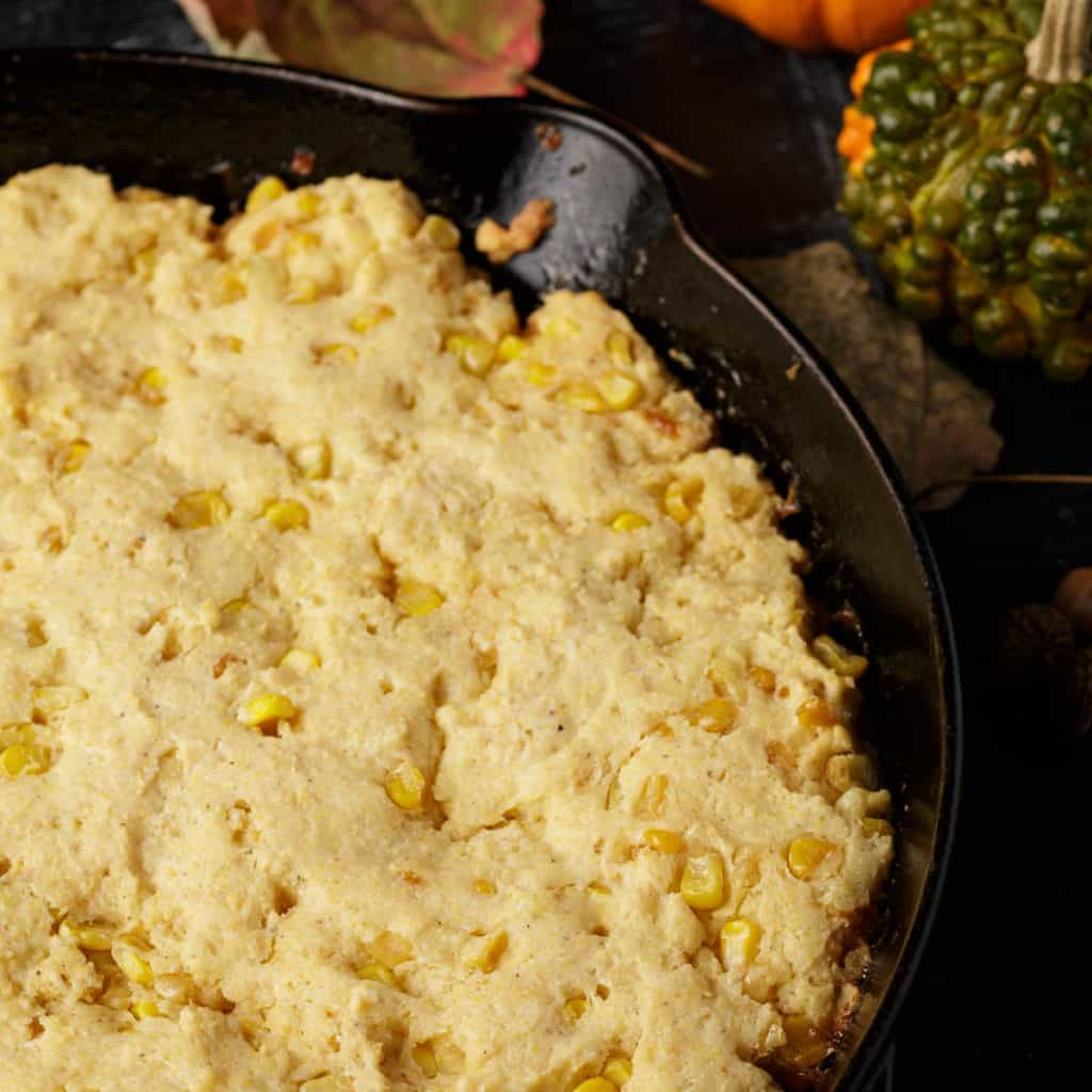 An iron skillet with cornbread with corn