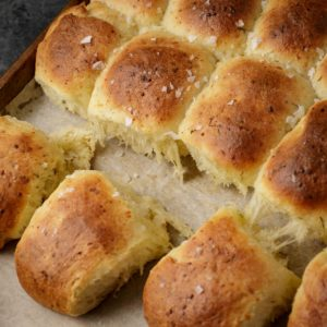 Dill and gruyere dinner rolls on a baking sheet