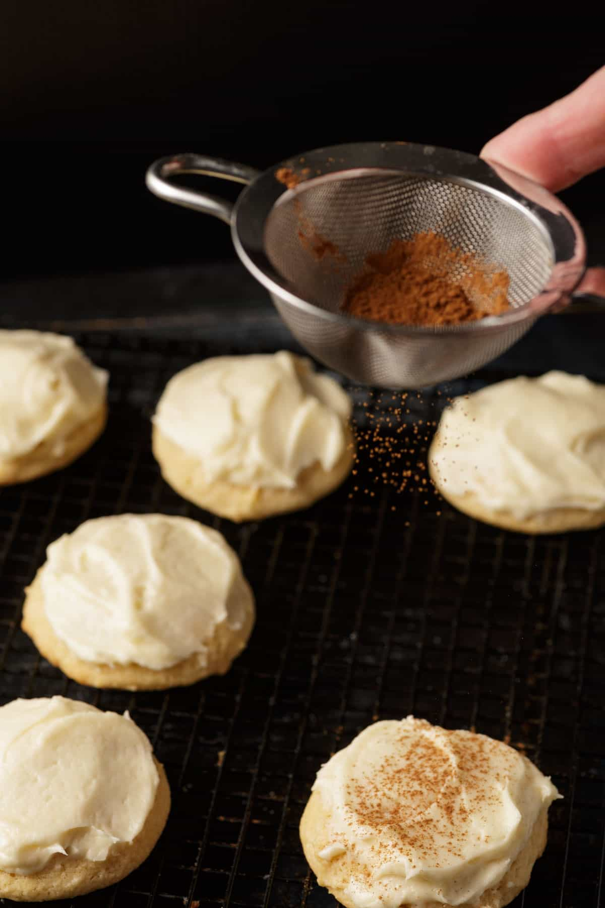 Cinnamon being sprinkled on frosted cookies