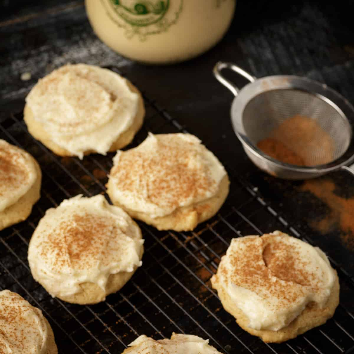 A rack of frosted eggnog cookies with cinnamon for sprinkling