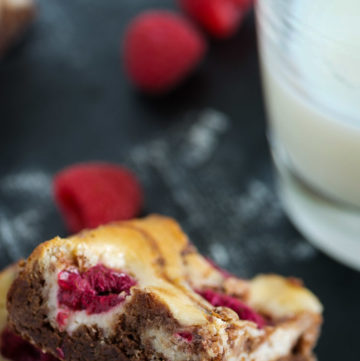 Cream cheese brownies with raspberries and a glass of milk