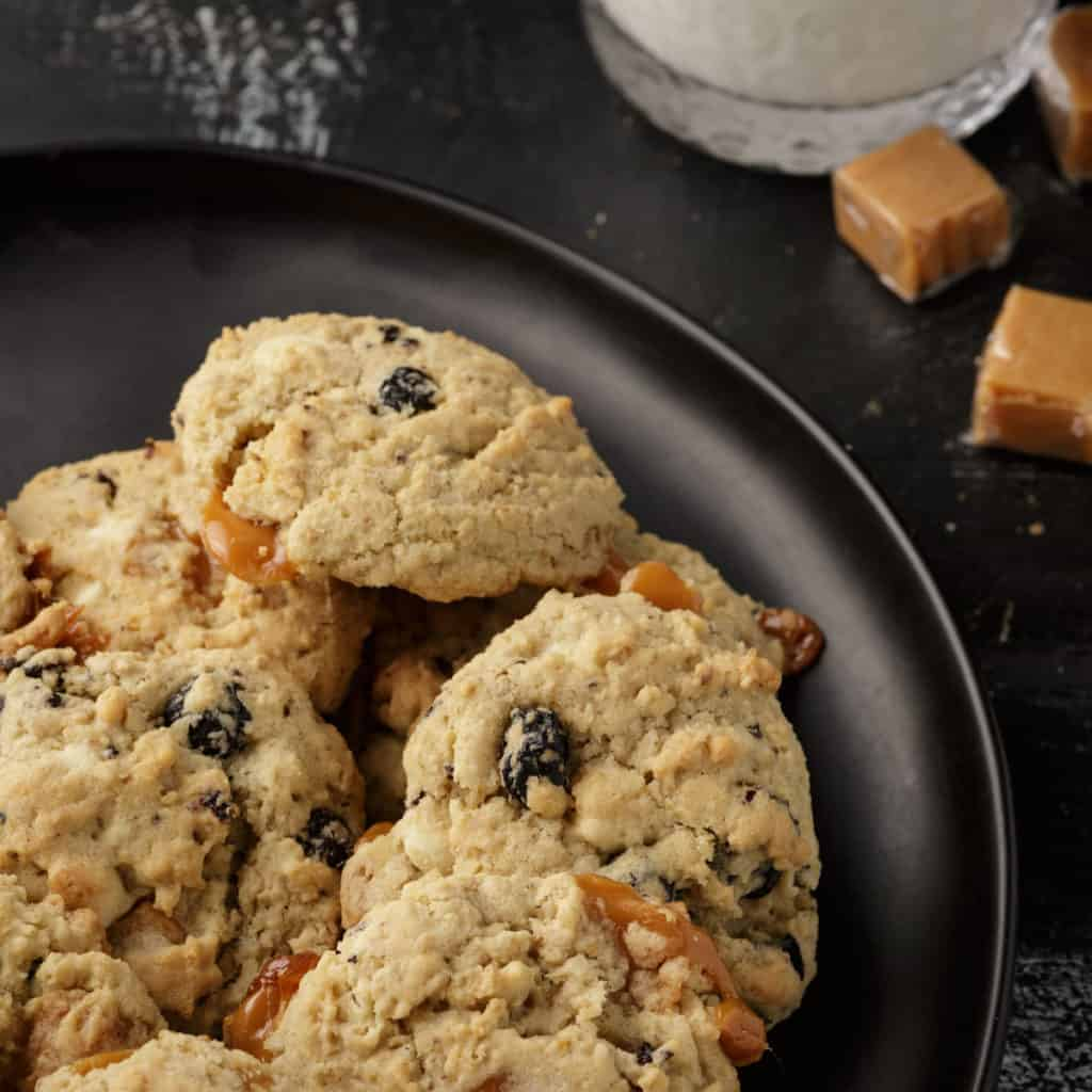 Blueberry oatmeal cookies on a plate with a glass of milk