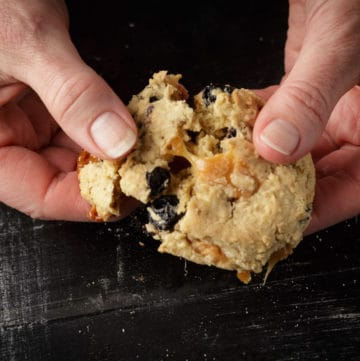 A blueberry white chocolate cookie being pulled apart